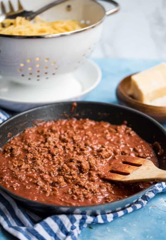 Bolognese Sauce in einer Pfanne mit Holzlöffel