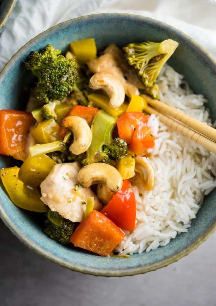 Hähnchen mit Gemüse und Cashews und Reis in einer hellblauen Schüssel von oben fotografiert