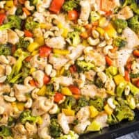 Hähnchen mit Cashews und buntem Gemüse auf einem Backblech von oben fotografiert
