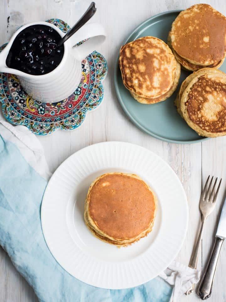 Proteinpancakes mit Heidelbeersauce und weitere Pancakes auf einem grauen Teller, von oben fotografiert