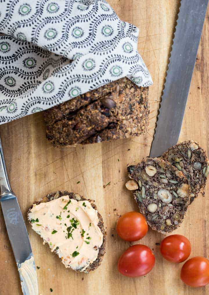 Low Carb Brot von oben fotografiert. Zwei Scheiben abgeschnitten, eine mit Frischkäse bestrichen