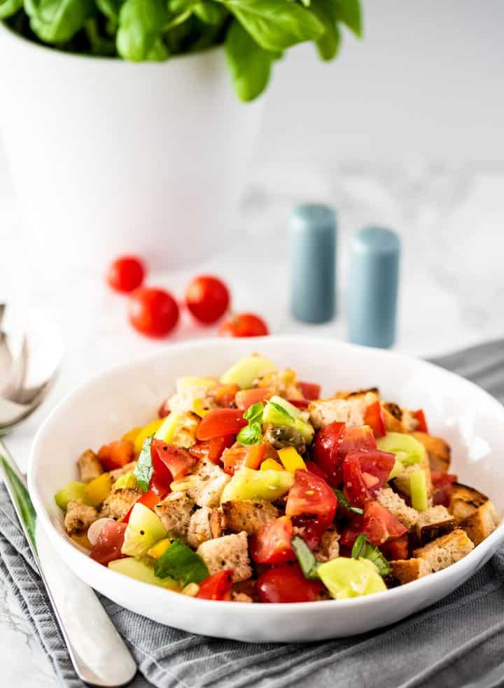 Italienischer Brotsalat in einer weißen Schüssel mit Tomaten und Basilikum im Hintergrund