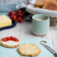 Frühstückstisch mit Kaffee, Brötchen im Korb und Butter