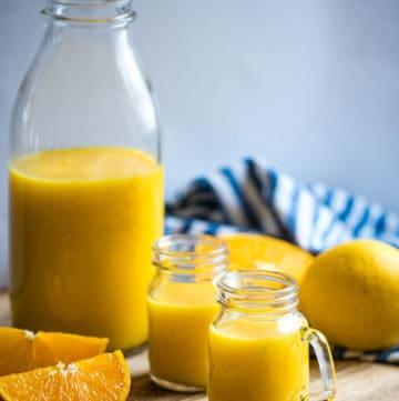 Ingwer Shot in einer Glasflasche mit 2 kleinen Shotgläsern und Früchten davor