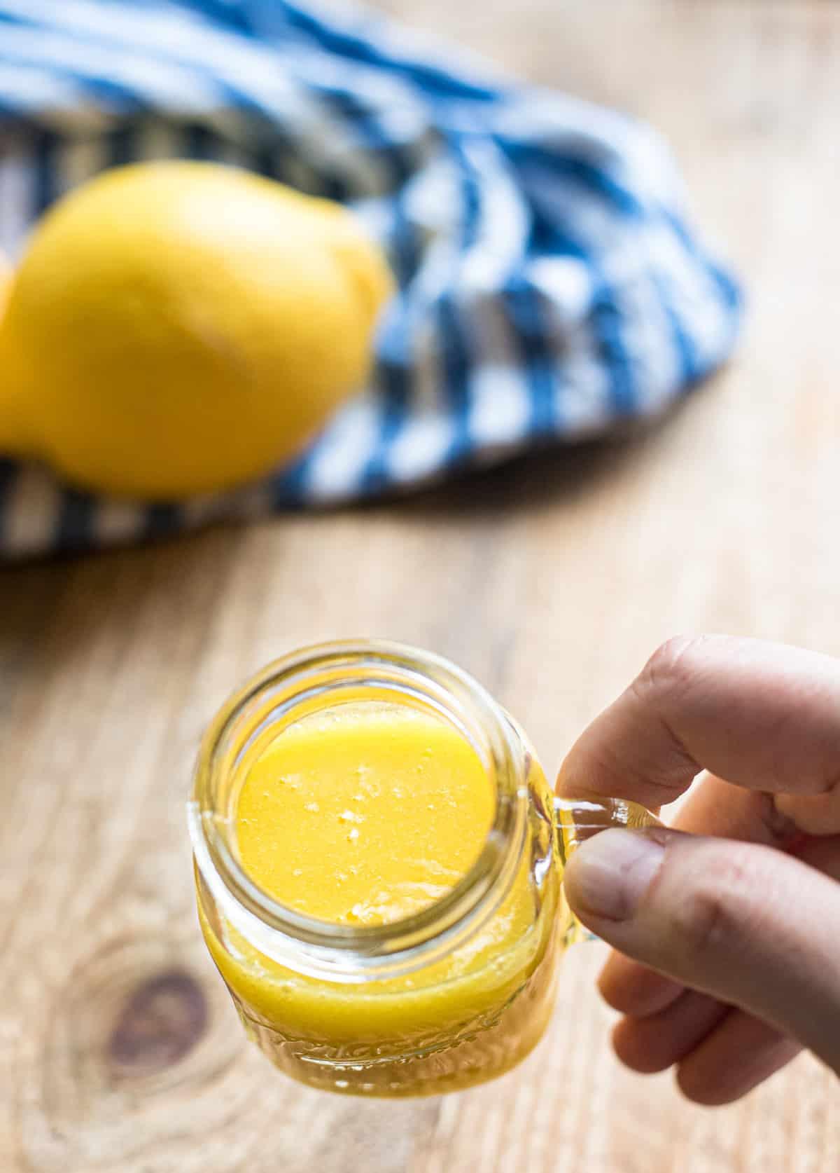 Ingwer Shot mit Orangen in einem kleinen Henkelglas, festgehalten