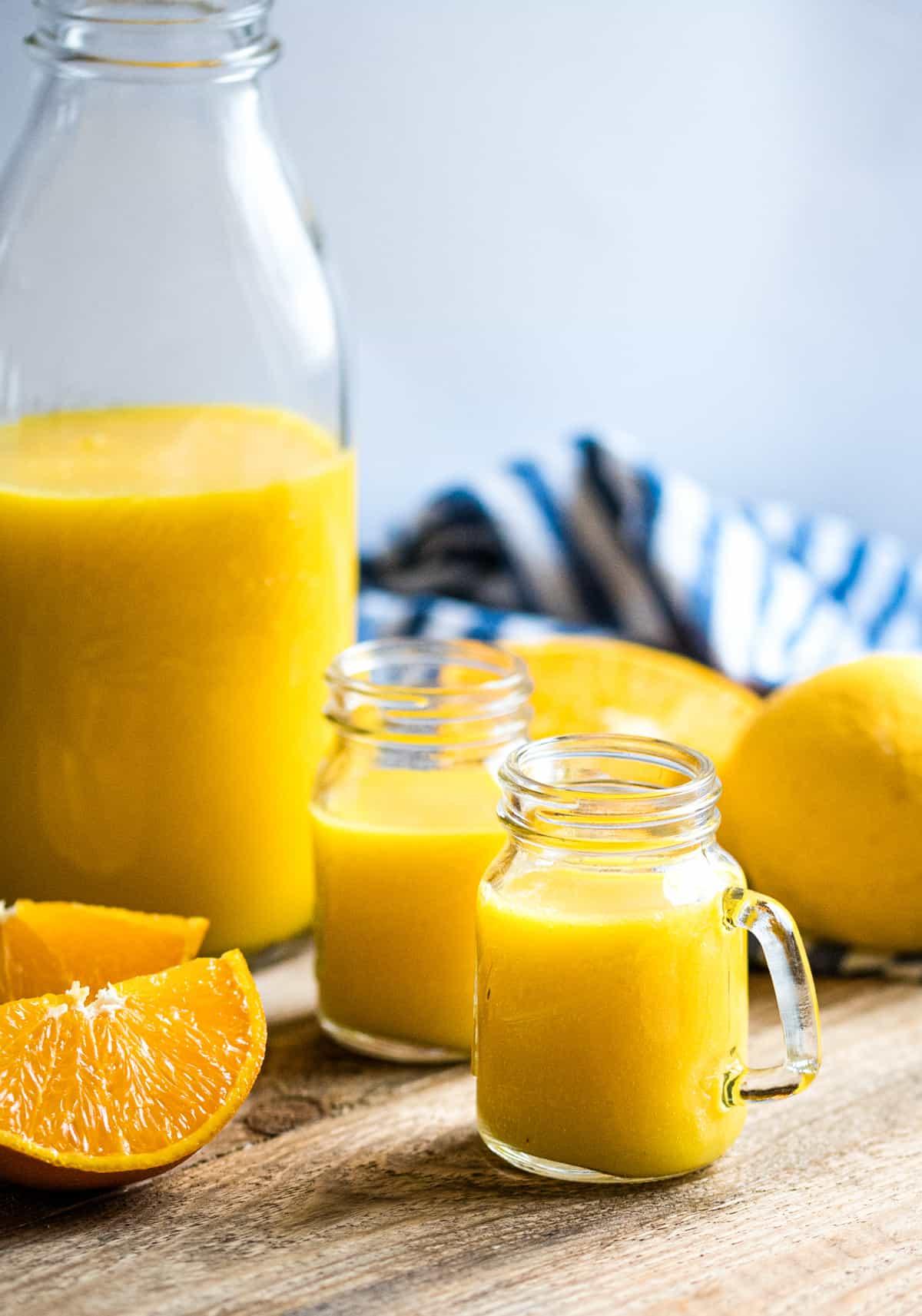 Zwei Gläser und eine Glasflasche mit Ingwer Orangen Shot