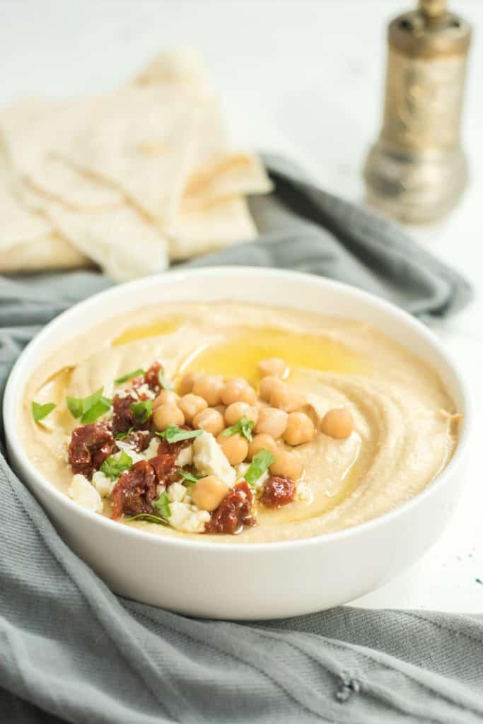 Hummus mit Kräuter, getrockneten Tomaten und Kichererbsen in einer weißen Schüssel, 45° Fotografiert