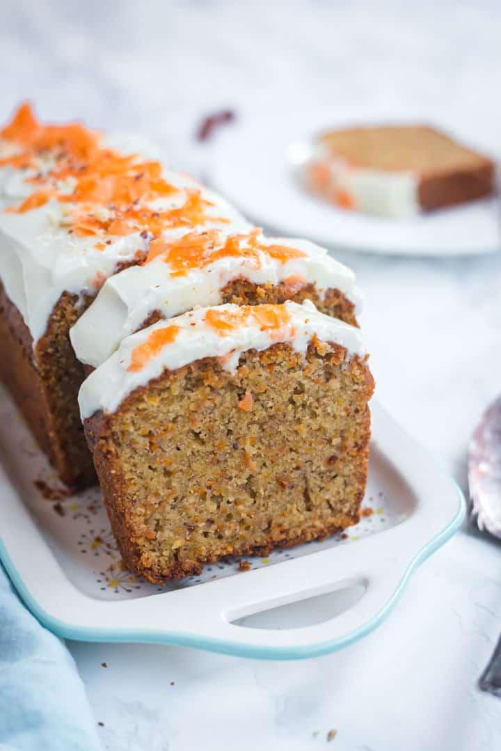 Karottenkuchen auf einer Kuchenplatte von vorne angeschnitten fotografiert