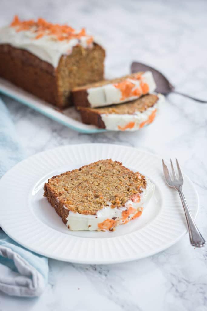 Karottenkuchen mit Guss. Ein Stück vorne auf einem weißen Teller, Kuchen im Hintergrund