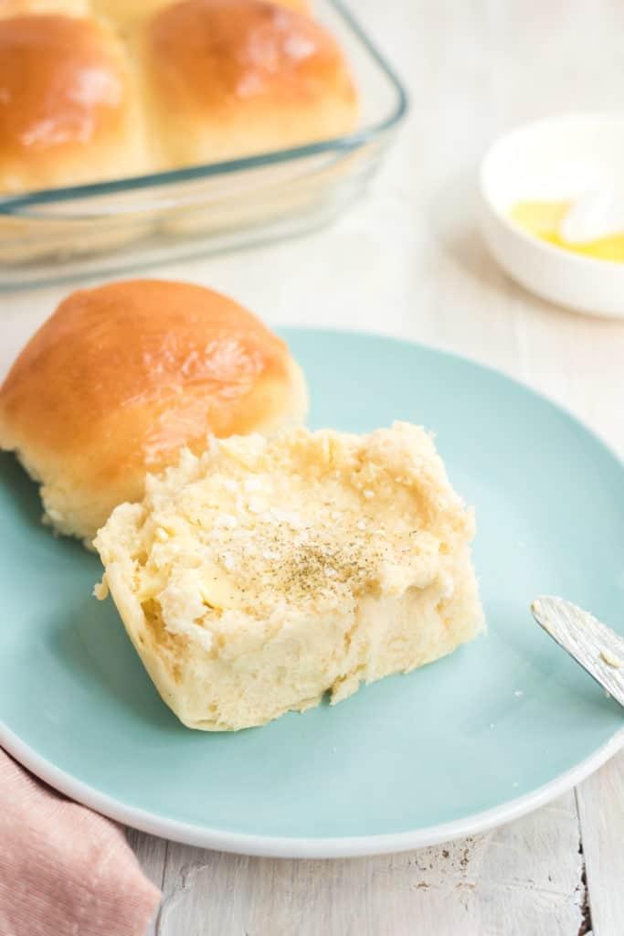 Dinner roll auf einem hellblauen Teller, halbiert und mit Butter bestrichen