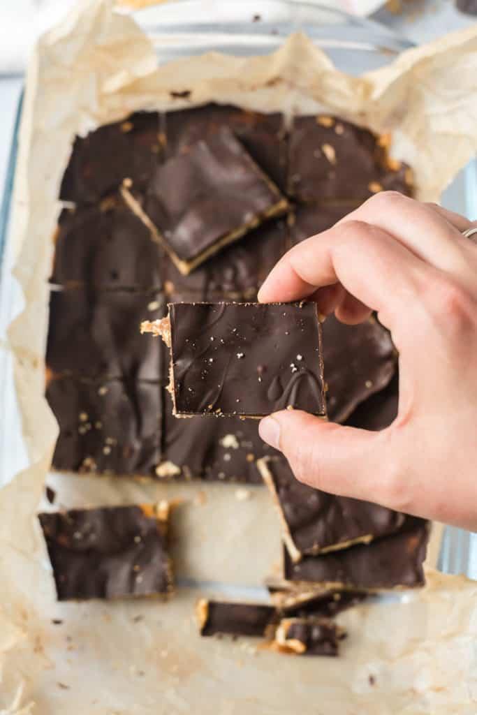 Hand hält einen Chocolate Caramel Cracker über der Form mit weiteren Stücken