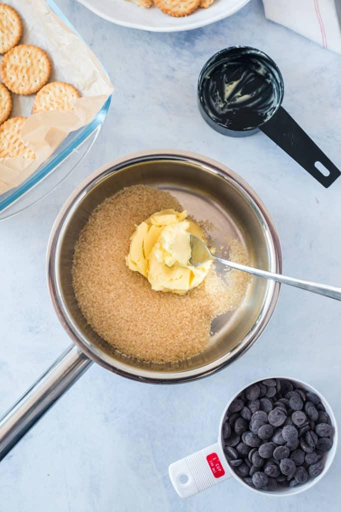 Brauner Zucker und Butter in einem Edelstahltopf. Von oben fotografiert