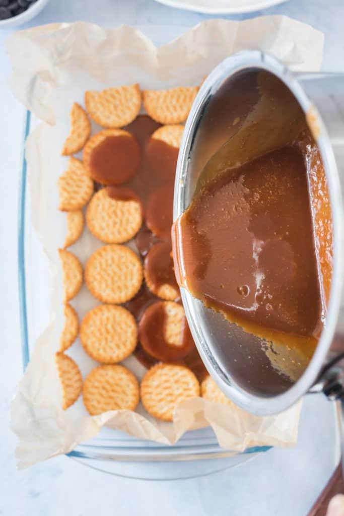 Karamellsauce wird auf die Cracker in einer Glasform gegossen. Von oben fotografiert
