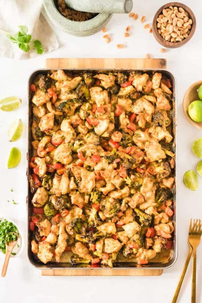 Hähnchen mit Erdnuss-Currysauce und Gemüse auf einem Backblech von oben fotografiert