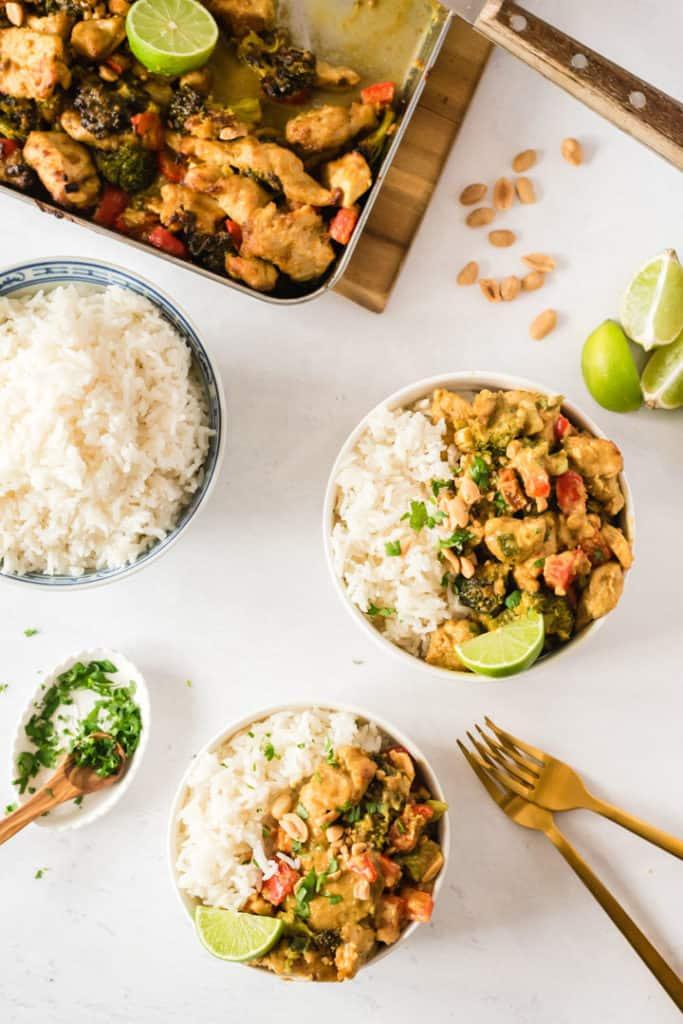 Zwei Schüsseln mit Saftiges Hähnchen mit Erdnuss-Currysauce mit Reis und Koriander. Von oben fotografiert