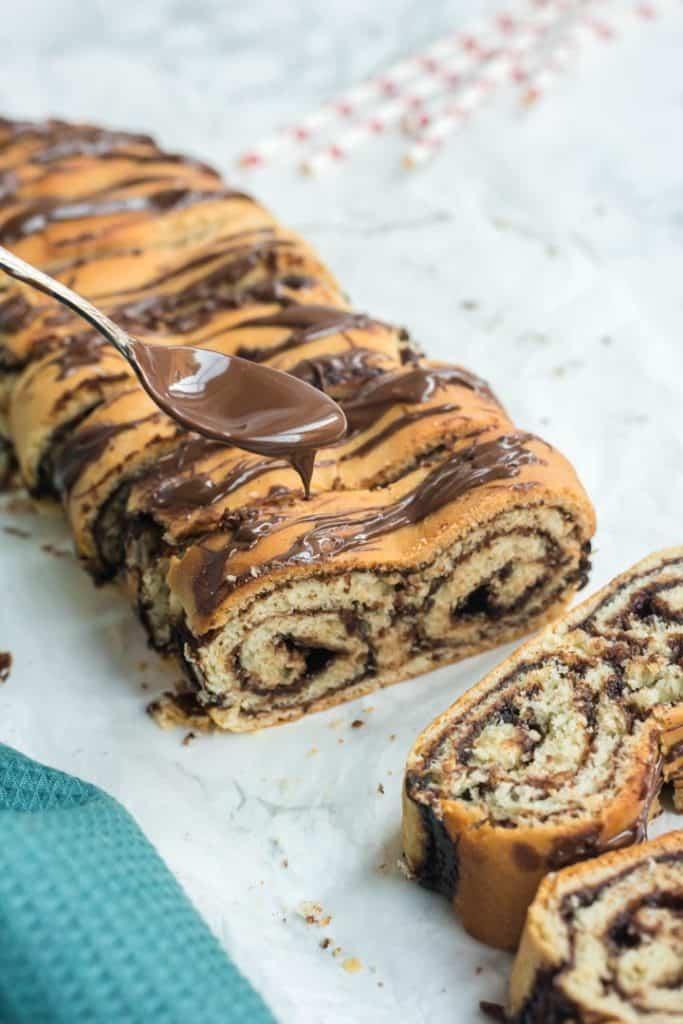 Nutella Brot in Scheiben auf weißem Pergamentpapier, Löffel mit tropfendem Nutella