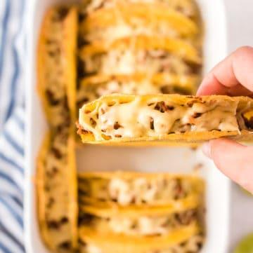 überbackene Tacos in weißer Auflaufform, einer in Hand