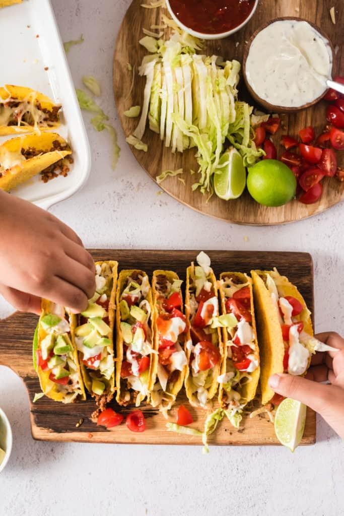 7 überbackene Tacos auf einem Holzbrett, zwei Hände nehmen sich je einen