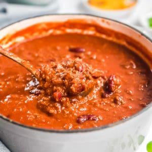 Chili in einem hellgrauen Topf, auf einer Suppenkelle