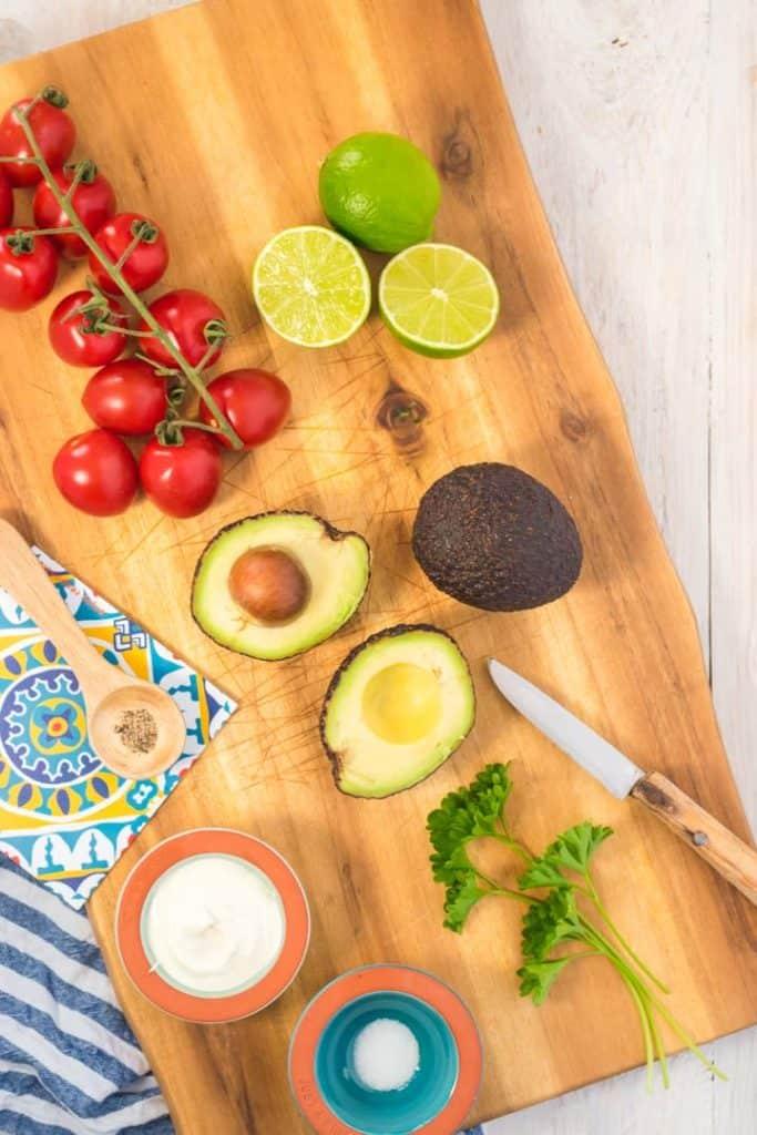 Zutaten für die Guacamole auf einem Holzbrett von oben fotografiert