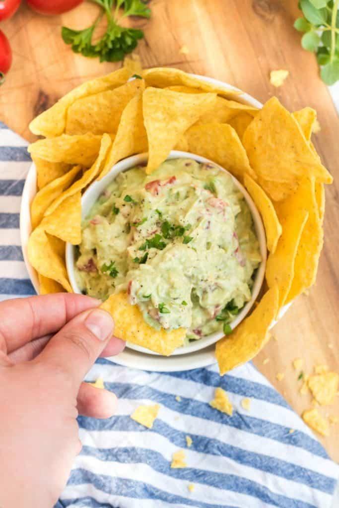Guacamole mit Nacho Chips in einer weißen Schüssel, Hand dippt Chips