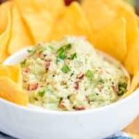 Guacamole mit Nacho Chips in einer weißen Schüssel