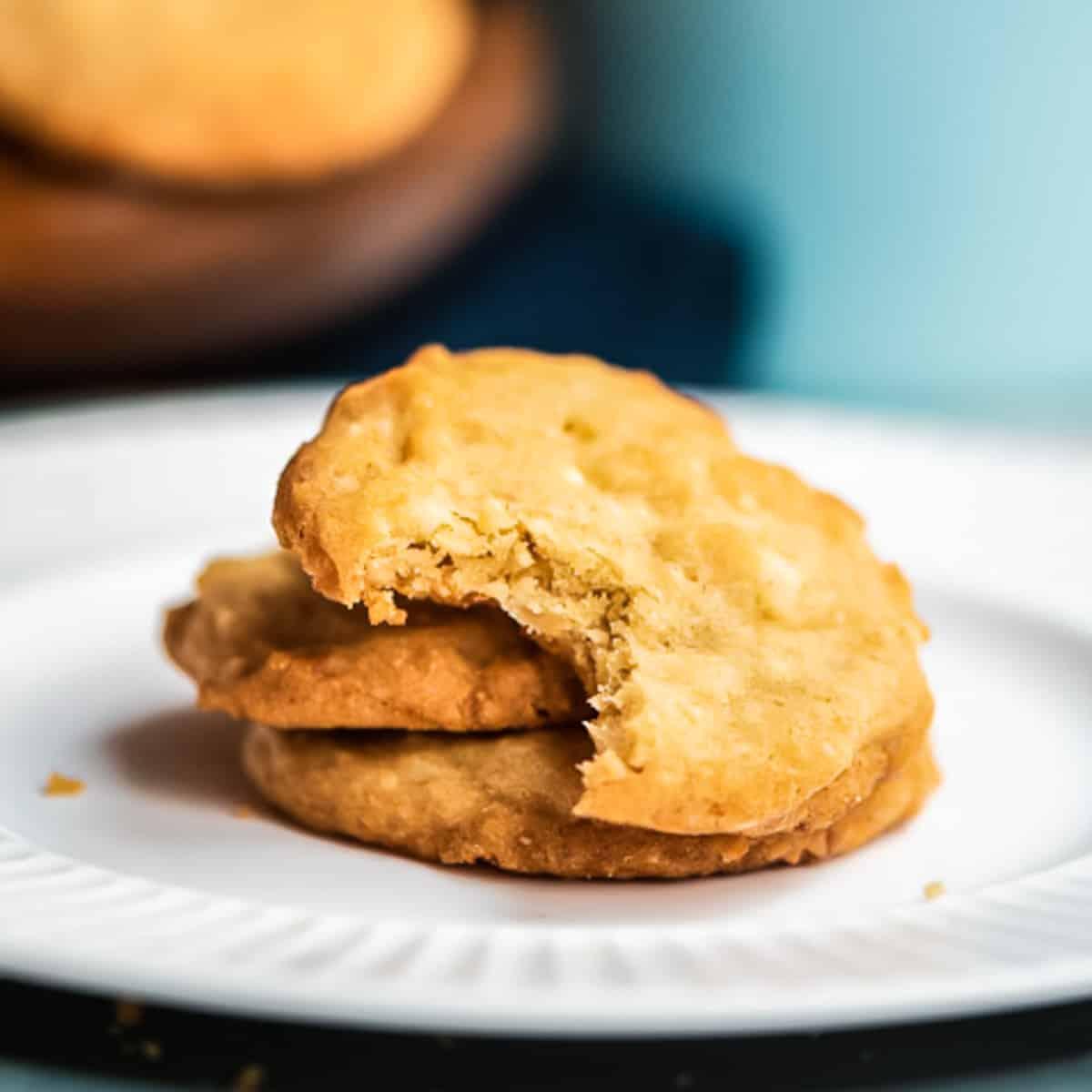 drei Macadamia Cookies mit weißer Schokolade auf einem weißen Teller, der oberste Keks angebissen