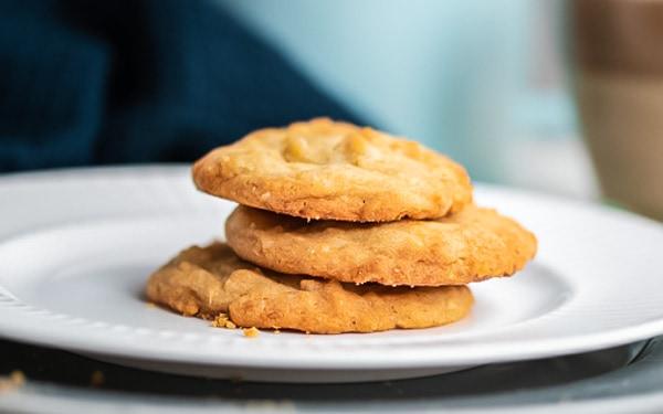 Teller mit drei Macadamia-Keksen mit weißer Schokolade