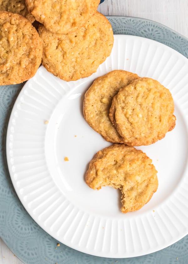 drei Macadamia Kekse auf einem weißen Teller, einer angebissen, von oben fotografiert