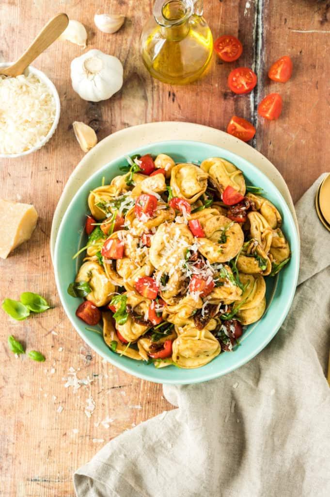 Tortellini-Salat in türkisfarbener Schale von oben
