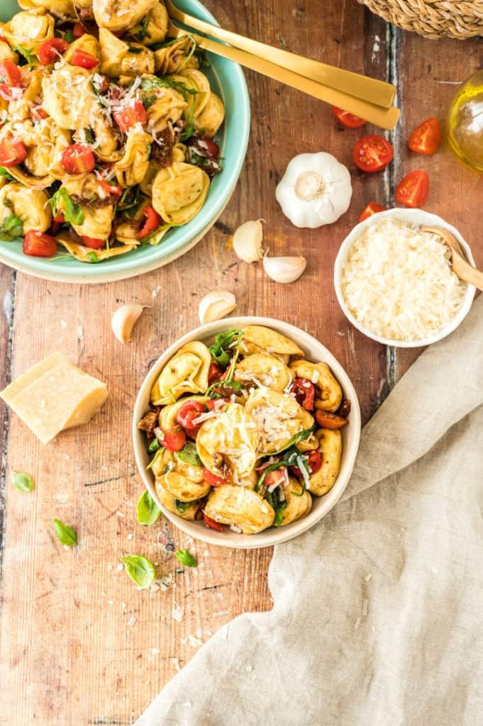 Tortelli-Salat in servier- und kleiner Schüssel von oben