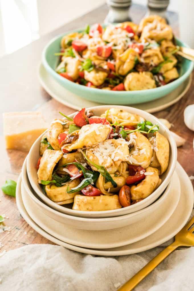 Tortellini-Salat in beiger Schale mit großer Schale im Hintergrund