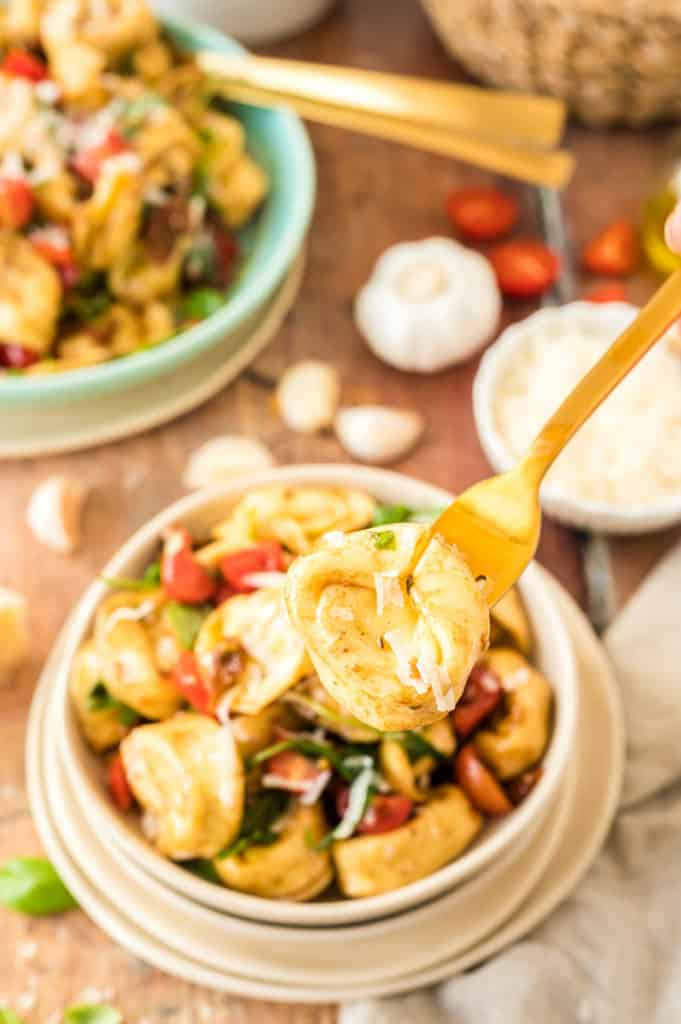 Tortellini auf eine Gabel aufgespießt, Tortellin-Salat im Hintergrund
