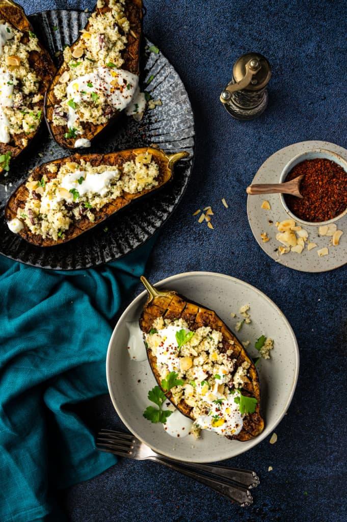 Auberginemit Bulgur auf einem hellen Teller, mehr Auberginen auf dunklem Teller, von oben