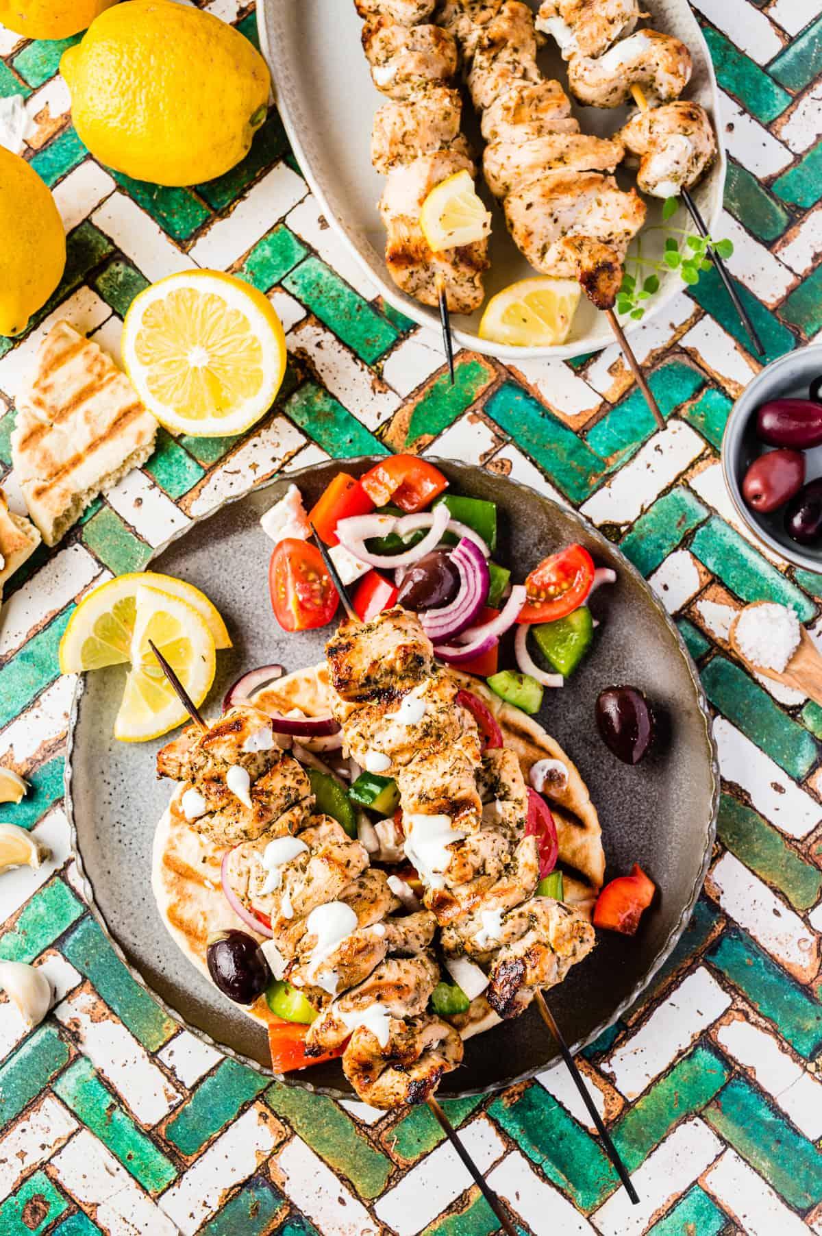 Souvlaki-Spieße auf Pita Brot mit Griechischem Salat auf dunklem Teller