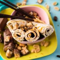 Ice-Rolls mit Karamellsauce und Erdnüssen in rosa schale