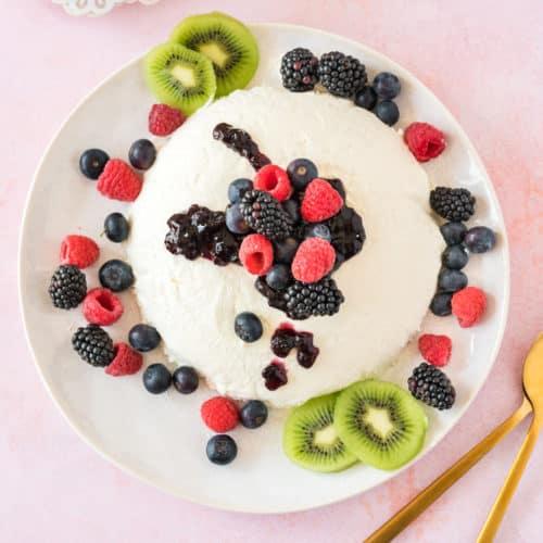 Joghurtbombe mit frischen Beeren auf weißem Teller von oben fotografiert