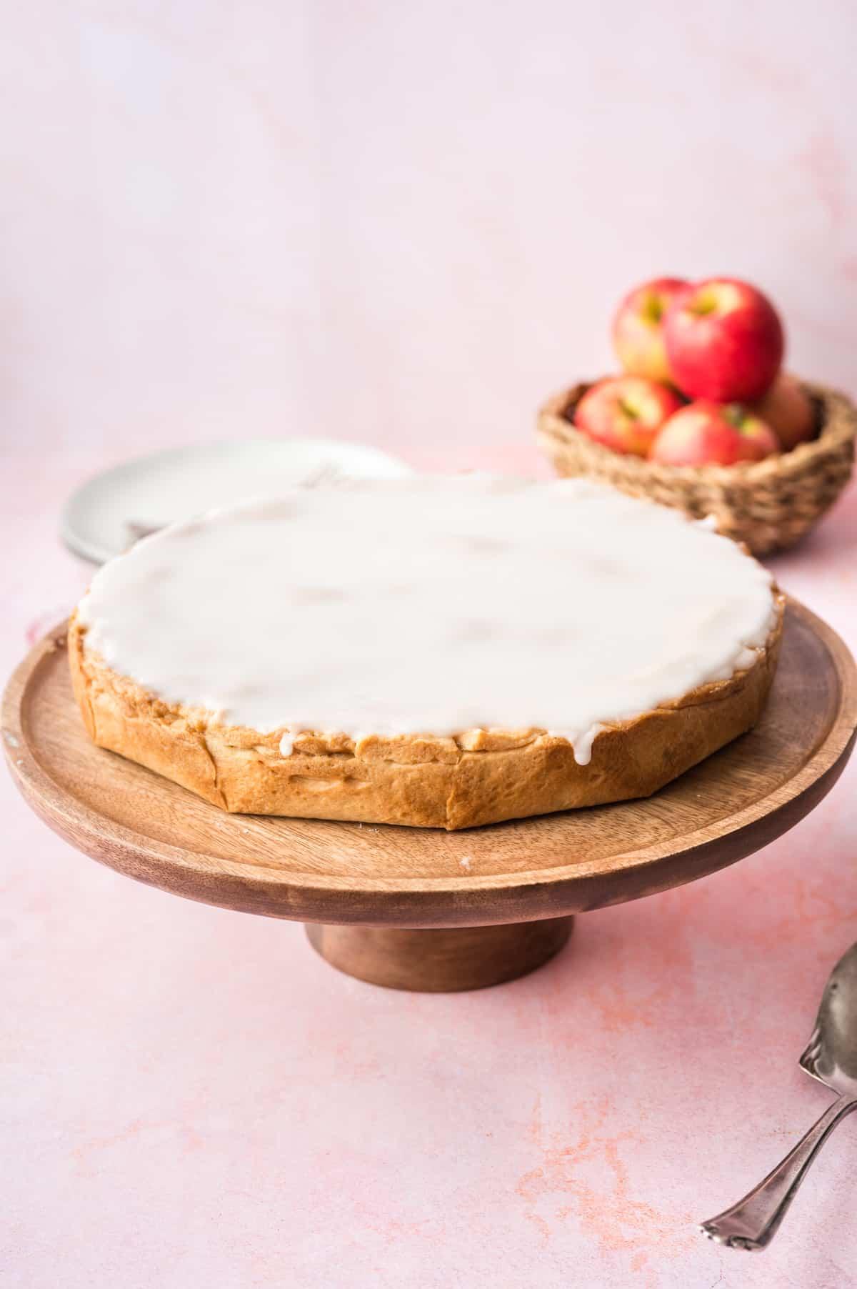Apfelkuchen mit Zuckerguss auf Holztortenplatte