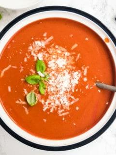 Tomatensuppe in weißem Topf mit Basilikum und Parmesan, von oben