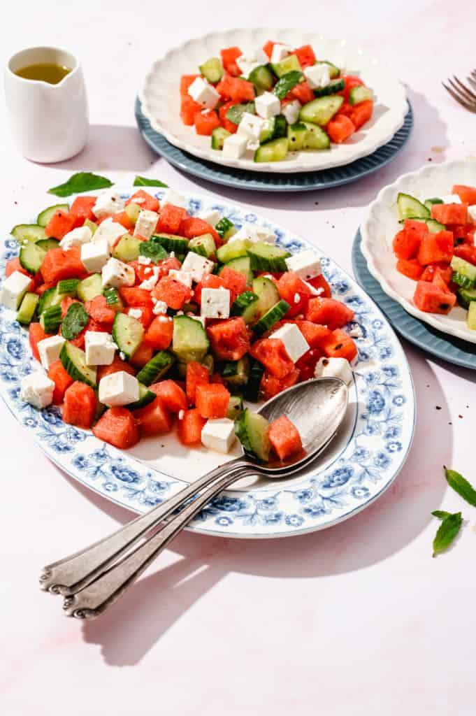 Wassermelonensalat auf ovaler weißer Platte mit 2 Löffeln
