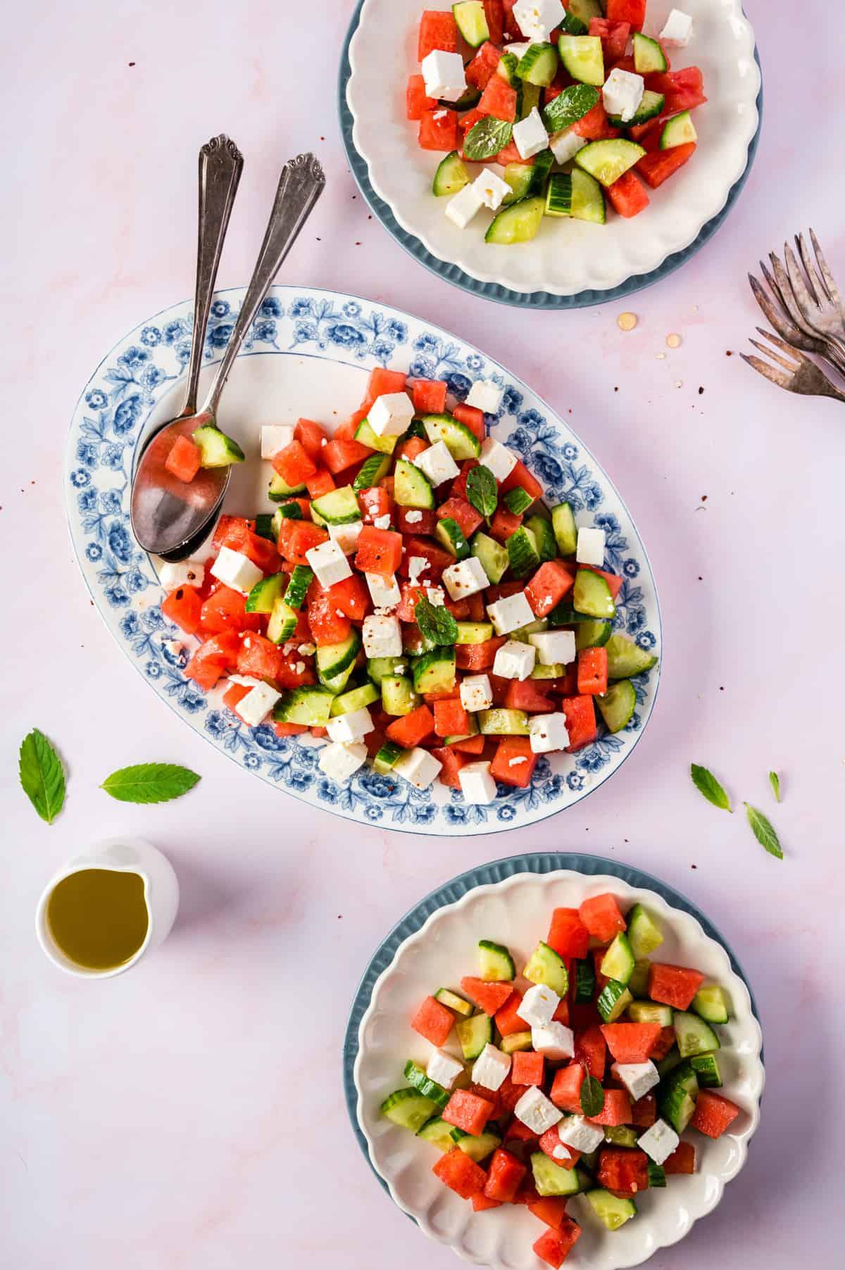 Ovale Schale mit Wassermelonensalat und zwei helle Teller, flatlay