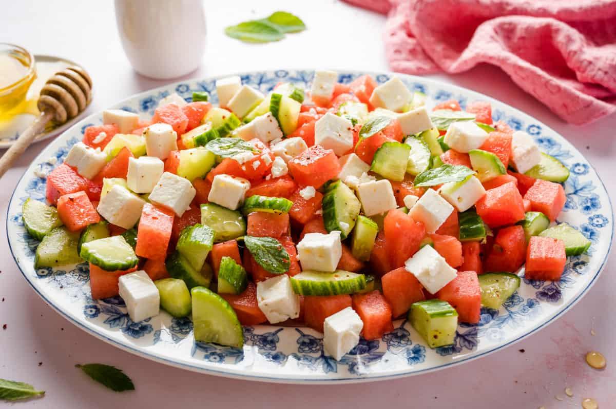 Wassermelonensalat auf einem ovalen Teller mit blauem Rand