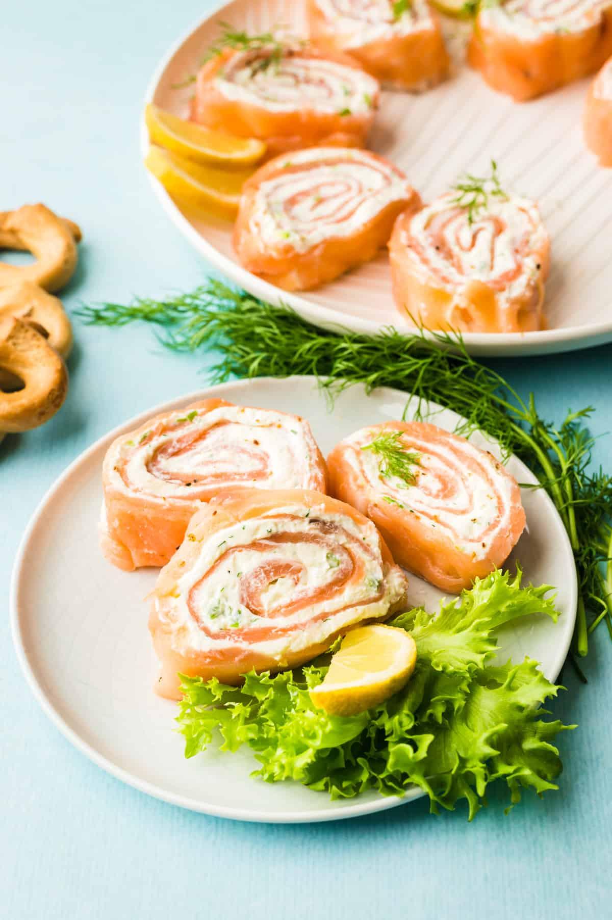 Drei Lachsröllchen auf einem weißen Teller mit Salatdeko