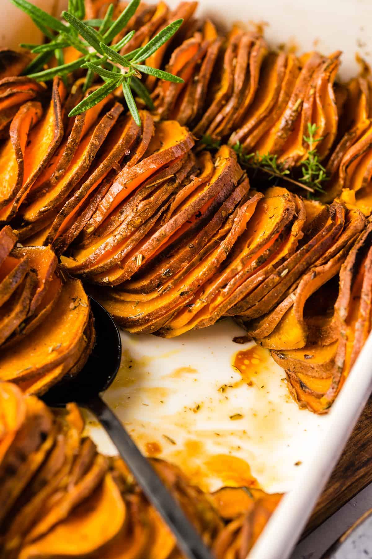 Gebackene Süßkartoffeln in Scheiben in weißer Auflaufform